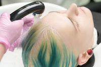 Professional hair salon, hairstylist washing customer head with green hair color