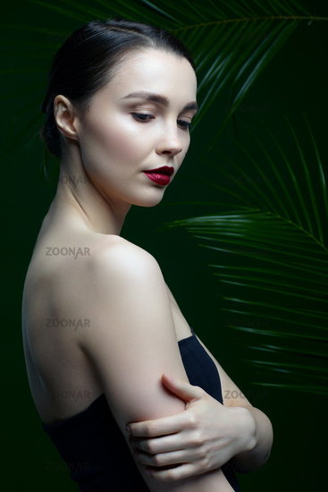 Romantic female on a background of palm leaves with hand on shoulder