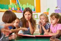 Gruppe Kinder und Betreuerin lesen in einem Kinderbuch