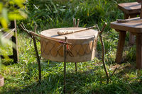North American Indian drum made of rawhide with bat ready to play in a meadow