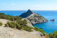 Summer mountain seascape - a mountain path to a rocky promontory in the middle of green trees against the background of the sea going to the horizon and the blue sky on a sunny day