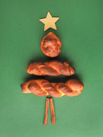 Yeast pastry decorated as Christmas tree on a green background