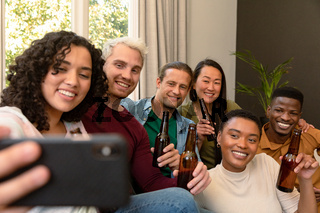 Group of happy diverse female and male friends drinking beer together and taking selfie