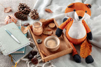 Hygge still life with a toy fox, a cup of coffee, autumn leaves and a journal