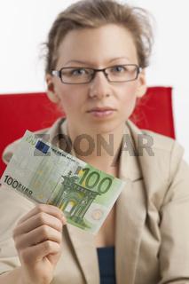 Junge Frau mit ernstem Blick hält hundert Euroschein