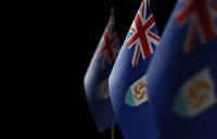 Small national flags of the Anguilla on a black background