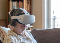 Senior adult woman watching an app on a modern VR headset