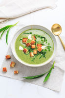 Ramson or bear leek soup with crouton and sour cream on white background