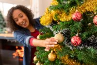 Happy african american woman hanging baubles on christmas tree