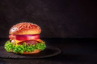 Burger on a black background with a place for text. Beef patty steak