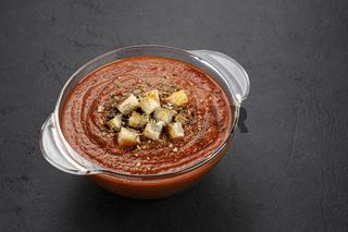 Bowl of tomato soup on black background