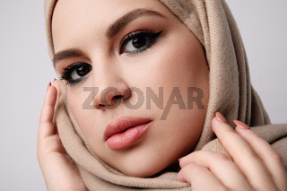 Close-up portrait of young arab muslim woman wearing beige hijab. Isolated.