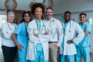 Portrait of group of diverse male and female doctors standing in hospital corridor smiling to camera