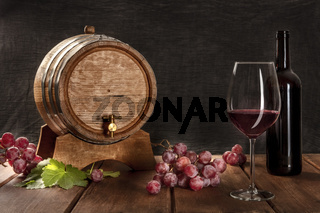 A glass of red wine with a bottle, a wine barrel, grapes, and vine leaves, on a dark rustic background