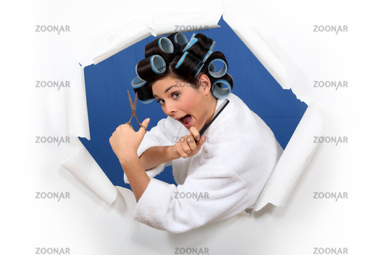 Woman in rollers with hairdressing scissors