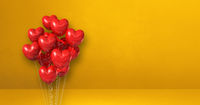 Red heart shape balloons bunch on a yellow wall background. Horizontal banner.