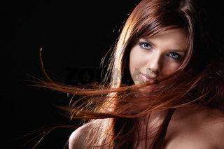 Developing hair beautiful girl on black background