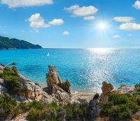 Summer sunshiny morning small sandy beach and rocky sea coast