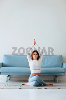 Middle age woman having yoga session at home