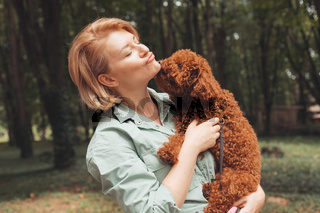 Cute yawning dog in female owner's arms