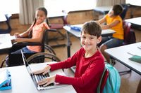 Portrait of caucasian boy with laptop smiling while sitting on his desk at elementary school