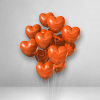 Orange heart shape balloons bunch on a white wall background