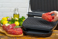 raw tuna steaks cooking on electric grill.