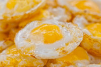 Stack of fried eggs focus on the center egg yolk