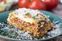 Portion Lasagne auf einem grünen Teller
