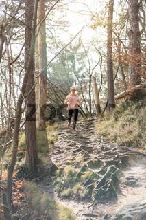 Active sporty woman listening to the music while running in autumn fall forest. Female runner training outdoor. Healthy lifestyle image of young caucasian woman jogging outside