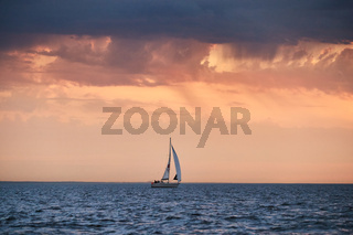 The lonely sailboat in a list goes by sea, the sky of pink color, the storm sky
