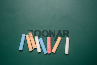 multicolored crayons on the background of green chalk school blackboard