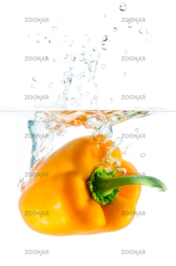 orange pepper falls into the water