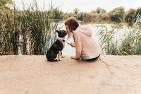 Little girl kissing her Boston Terrier dog on the lakeshore - Autumn scenery