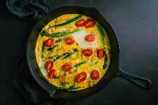 Delicious fritatta with green asparagus and cherry tomatoes in pan
