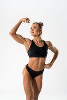 Smiling sportswoman in underwear showing muscular body