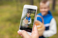 parent photographing grandson with mushrooms
