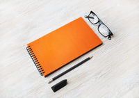 Orange notepad, glasses, pencil, eraser