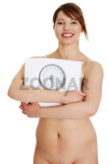 Young beautiful naked woman is holding weight.