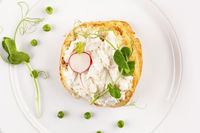 Tasty bread with cream cheese, peas and radish on white plate from above.