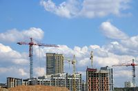 Construction cranes and houses under construction against the sky.