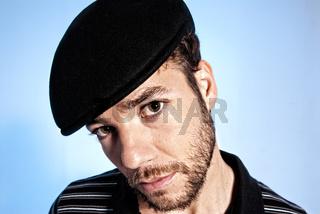 Young modern man portrait handsome hat blue background
