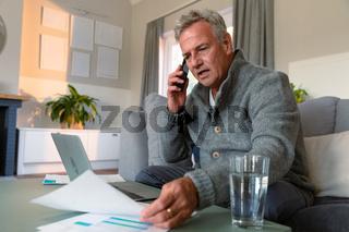 Focused caucasian senior man sitting on sofa, doing paperwork, making call and using laptop