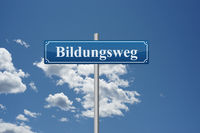German word educational path on road sign in front of sky education school