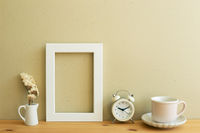 White photo frame, dry flower, clock, coffee cup on wooden table. beige wall background. home interior