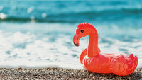 inflatable flamingos on beach with sea wave
