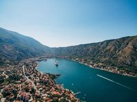 Kotor Bay from a bird's-eye view, aerial shot from a drone. Cruise liner moored in the waters of the bay, opposite the old city of Kotor. Roofs of houses in the city of Dobrota.