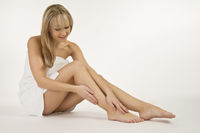 Blonde woman relaxes in foot care