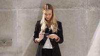 Businesswoman browsing cellphone near concrete wall