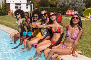 Diverse group of friends drinking beer and sitting at the poolside